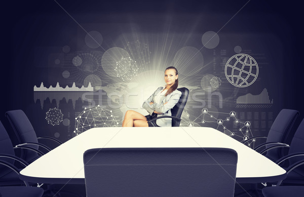 Business lady sitting at table with crossed legs and arms Stock photo © cherezoff