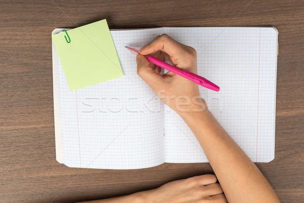 Open copybook with writing hand on table Stock photo © cherezoff
