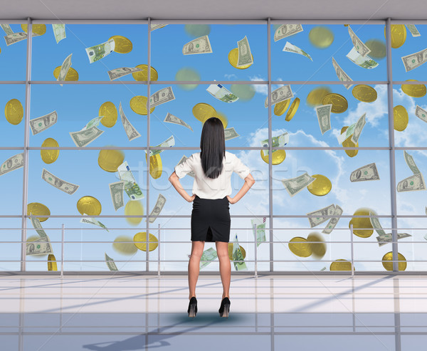 Businesswoman looking at flying money Stock photo © cherezoff