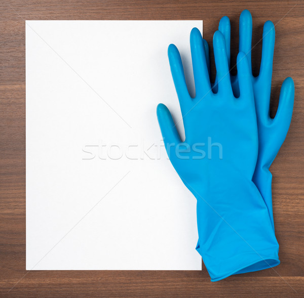 Leeres Papier blau Gummihandschuhe Holztisch Papier weiß Stock foto © cherezoff