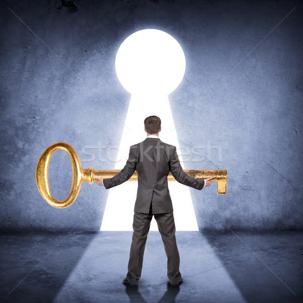 Businessman holding huge gold key, rear view Stock photo © cherezoff