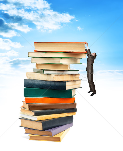 Businessman hanging on top of stack books Stock photo © cherezoff
