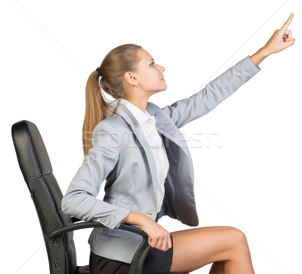 Businesswoman on office chair, pointing finger up and ahead  Stock photo © cherezoff