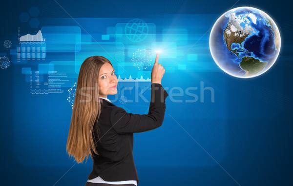 üzletasszony áll hát néz kamera kisajtolás Stock fotó © cherezoff