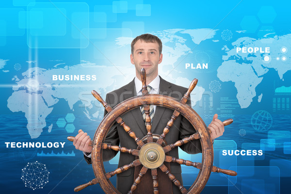 Man with steering wheel and business words Stock photo © cherezoff
