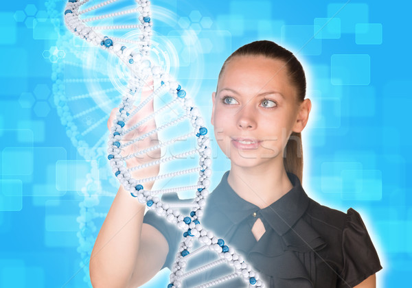 Beautiful young girl looks at model of DNA and presses her finger Stock photo © cherezoff