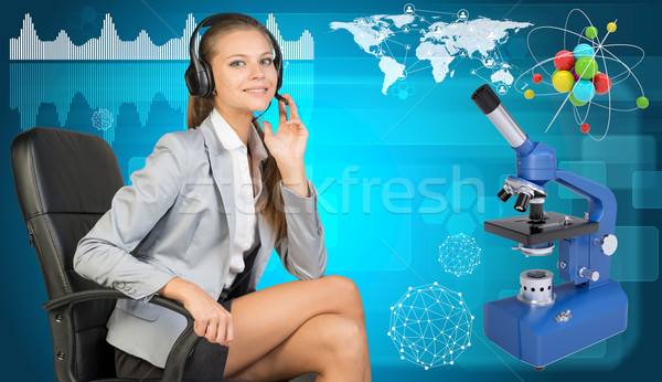 Businesswoman in headset, atom model and microscope Stock photo © cherezoff