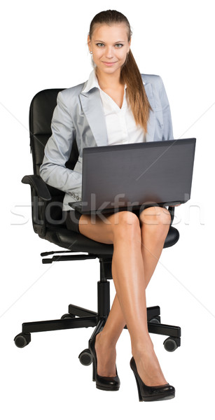 Businesswoman on office chair, with laptop Stock photo © cherezoff