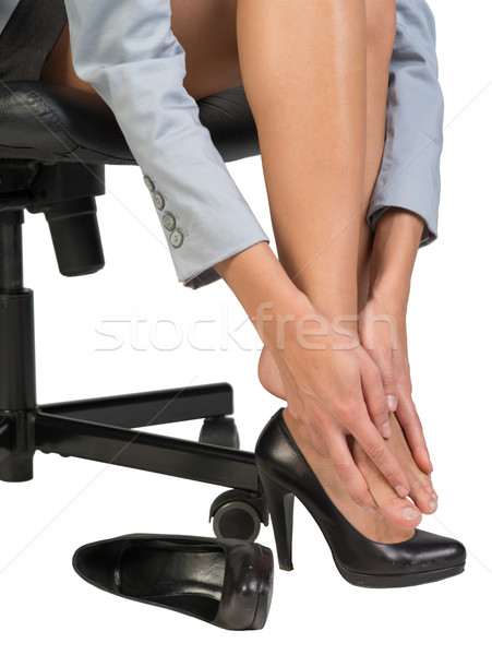 Businesswoman sitting on chair and massaging her feet Stock photo © cherezoff