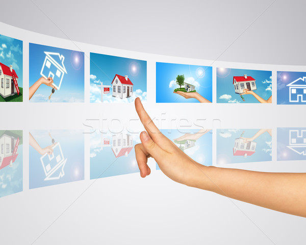 Subject homes for sale and rent. Finger presses one of virtual screens Stock photo © cherezoff