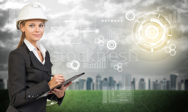Businesswoman holding clipboard. Blured city, grass and flying virtual elements Stock photo © cherezoff