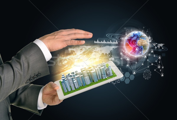 Man hands using tablet pc. Business city on touch screen. Earth with network near computer Stock photo © cherezoff
