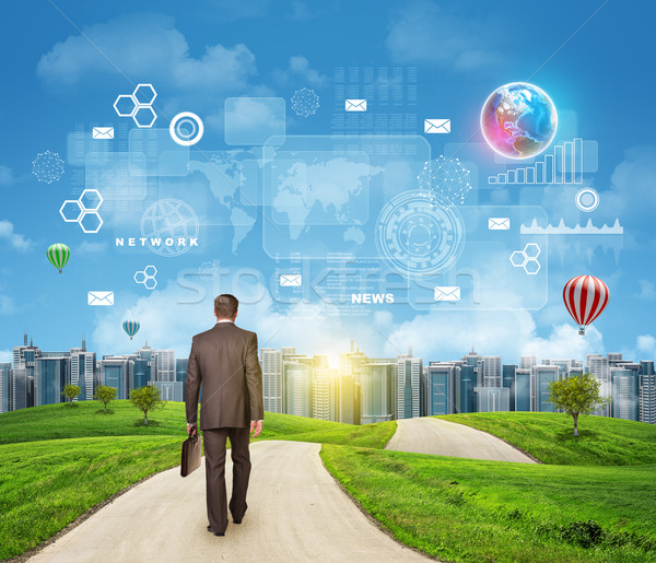 Businessman walks on road. Rear view. Buildings, grass field and sky with virtual elements Stock photo © cherezoff