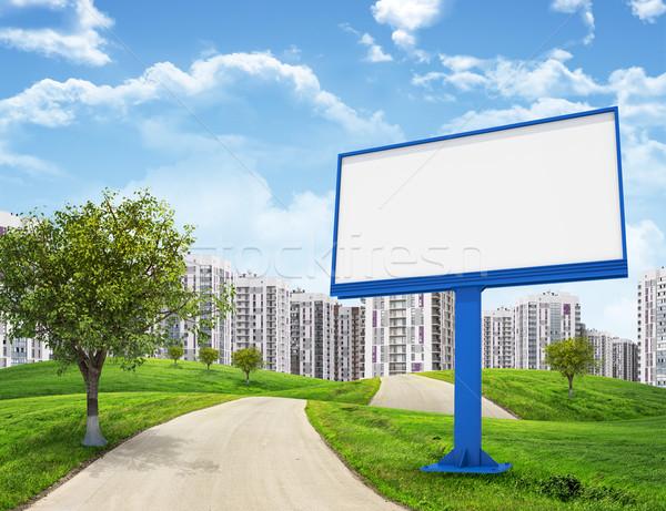 Blank billboard and tree by road running through green hills leading toward city, II Stock photo © cherezoff