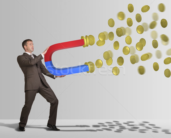 Businessman in suit holding big magnet and attracts money Stock photo © cherezoff