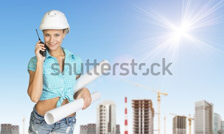 Woman in helmet holds white paper. Looking at camera, smiling. Green hills with road and buildings Stock photo © cherezoff