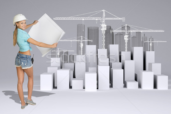 Girl in helmet showing empty paper sheet. Full lenght. White cubes with tower cranes Stock photo © cherezoff