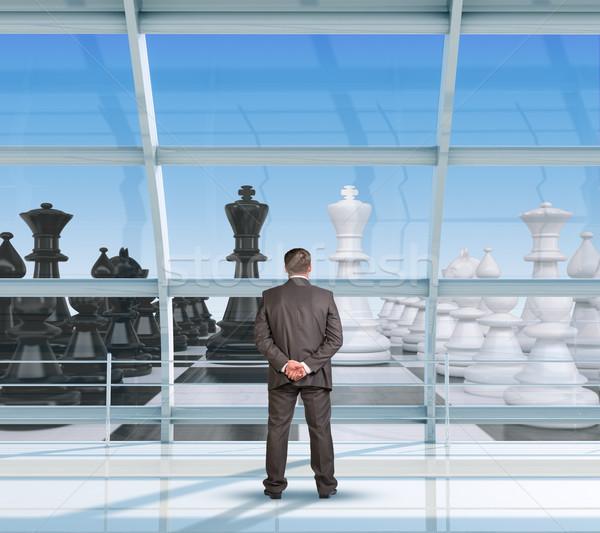 Businessman looking at chess Stock photo © cherezoff