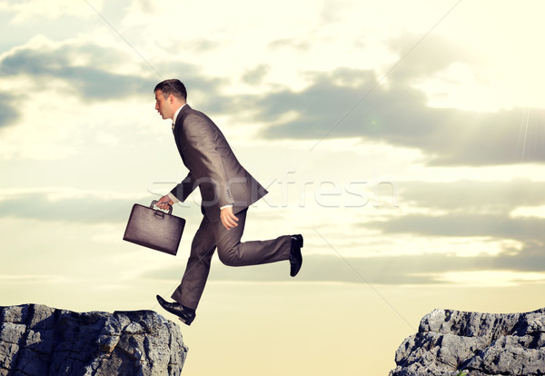 Businessman jumped over abyss Stock photo © cherezoff