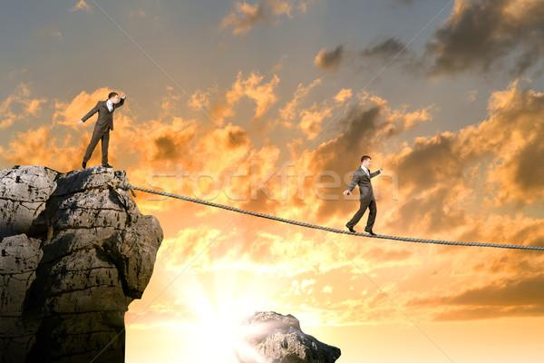 Empresário caminhada corda acima lacuna pôr do sol Foto stock © cherezoff