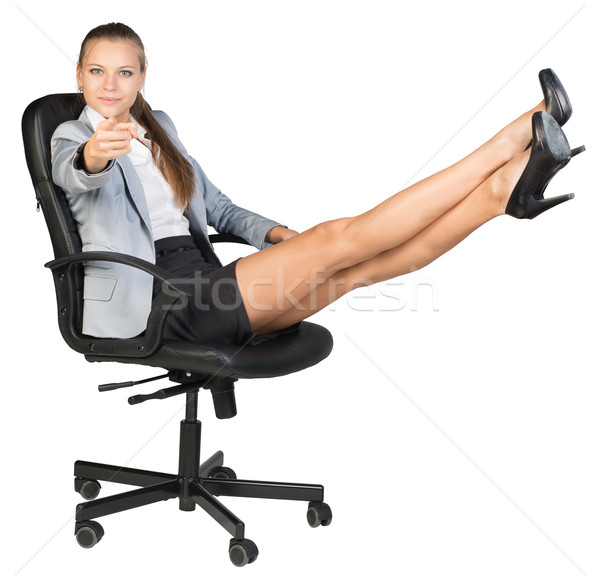 Businesswoman on office chair with her feet up, pointing finger at camera Stock photo © cherezoff