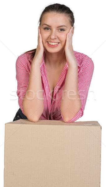 Woman resting her elbows on cardboard box Stock photo © cherezoff