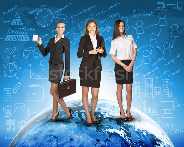Business womens in suits, blouses, skirts, smiling and looking at camera. Against backdrop of globe, Stock photo © cherezoff