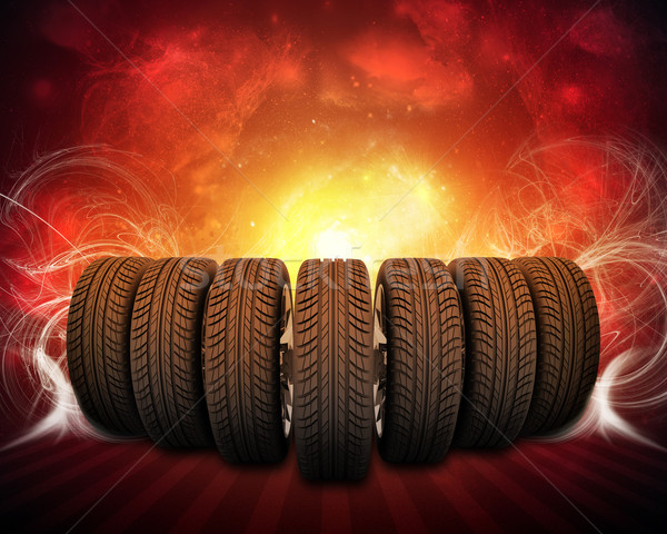 Wedge of new car wheels. Background is night sky and stripes at bottom Stock photo © cherezoff