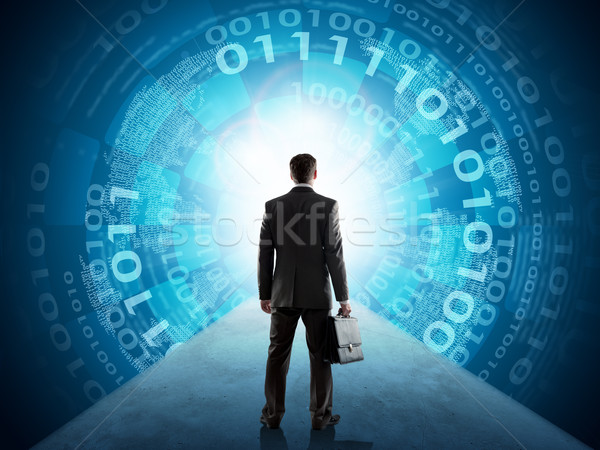Businessman standing in front of matrix background Stock photo © cherezoff