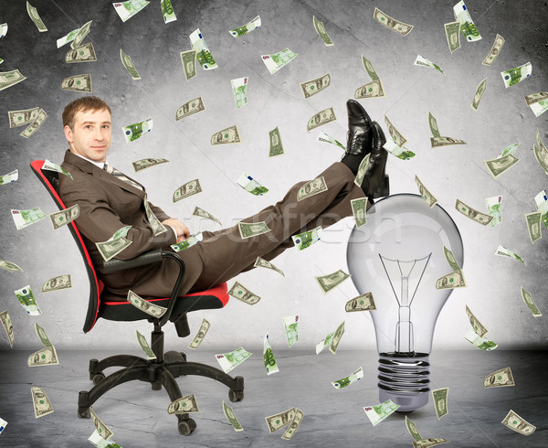 Businessman with light bulb and money rain Stock photo © cherezoff