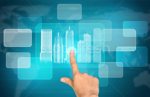 Humans hand pressing on virtual city model Stock photo © cherezoff