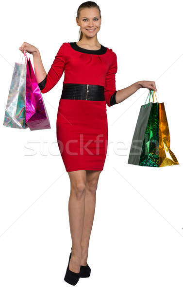 Woman with teeth smile handing bags up Stock photo © cherezoff