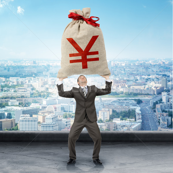 Businessman holding big moneybag with yen sign Stock photo © cherezoff