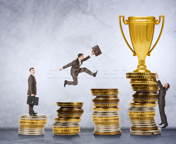 Businessman trying to get gold cup Stock photo © cherezoff