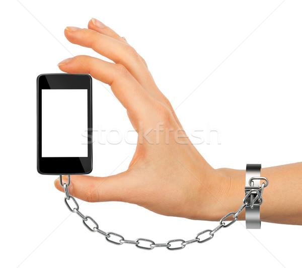 Chained female hand holding phone Stock photo © cherezoff