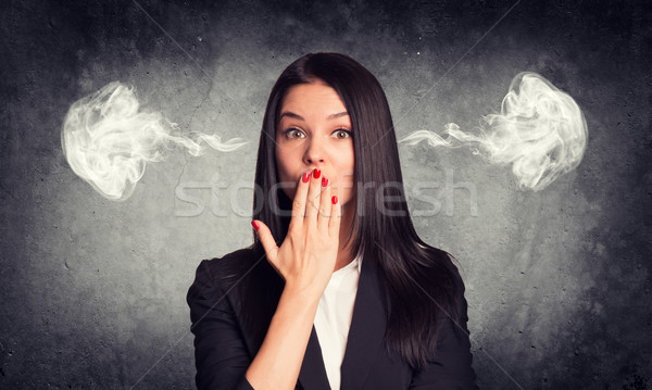 Kissing woman with steam from ears. Concrete gray as backdrop Stock photo © cherezoff
