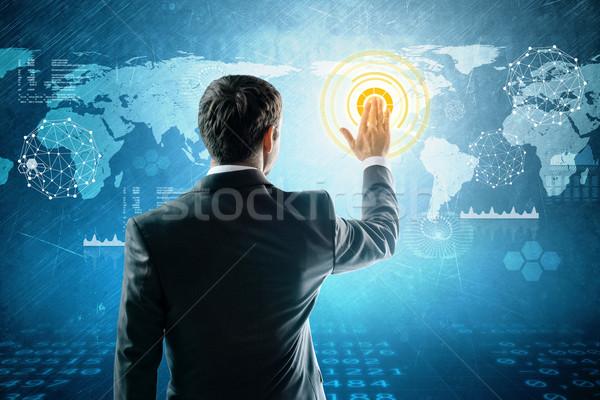 Businessman presses interactive world map Stock photo © cherezoff