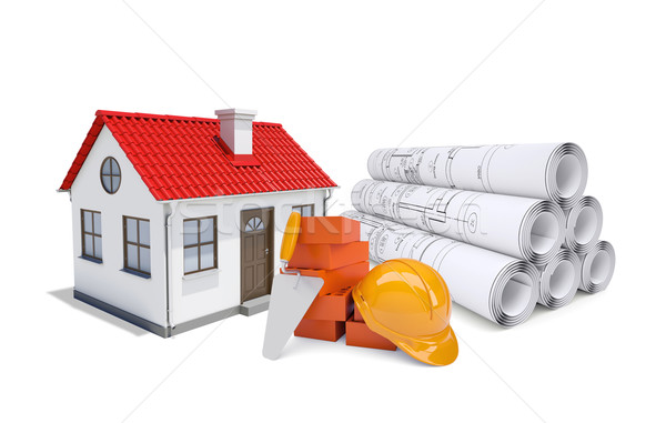 Small model house with red roof near scrolls of architectural drawings and work tools Stock photo © cherezoff