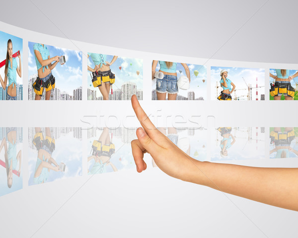 Women in background building construction. Finger presses one of virtual screens Stock photo © cherezoff