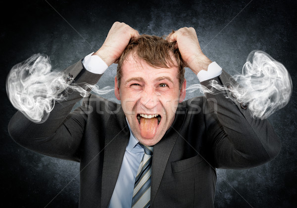 Businessman with smoke from his ears Stock photo © cherezoff