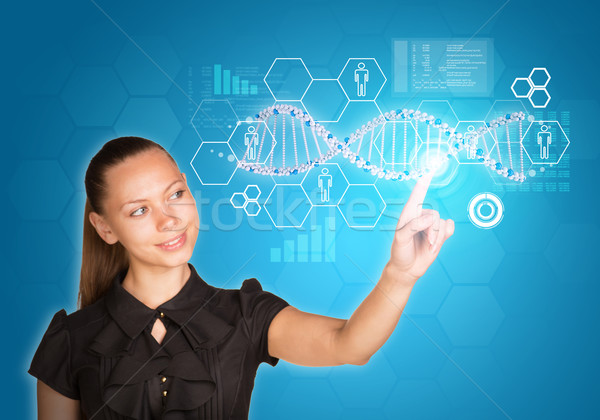 Beautiful young girl smiling head bent and presses finger on model of DNA Stock photo © cherezoff