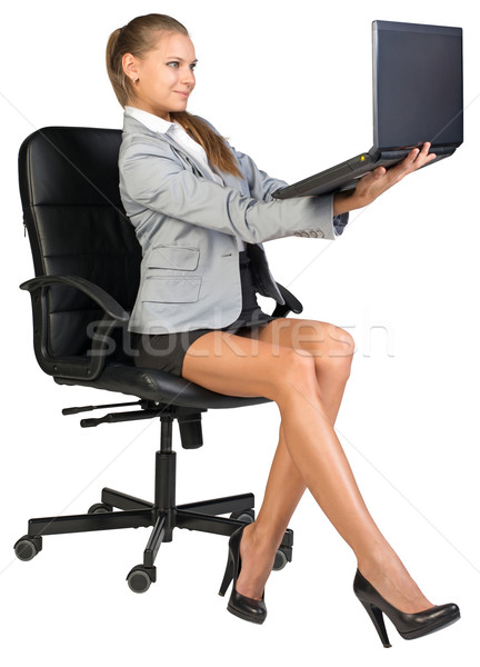 Stock photo: Businesswoman on office chair, holding laptop in her arms at eye level