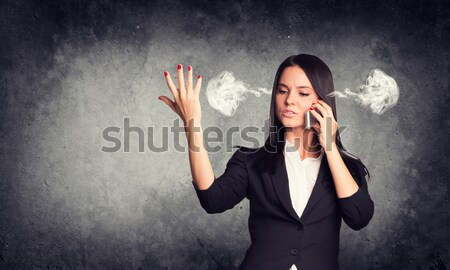 Frustrated woman holding finger to his temple, smoke from ears. Concrete wall in background Stock photo © cherezoff