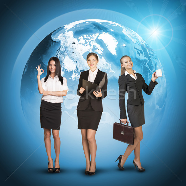 Business womens in suits, blouses, skirts, smiling and looking at camera. Against background of glob Stock photo © cherezoff