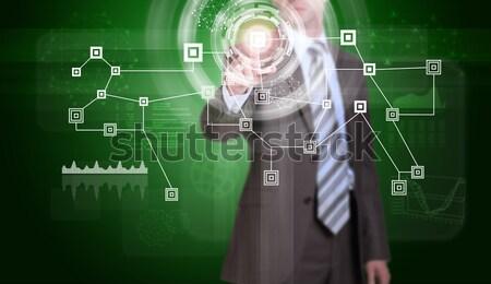 Imprenditore suit dito virtuale pulsante verde Foto d'archivio © cherezoff