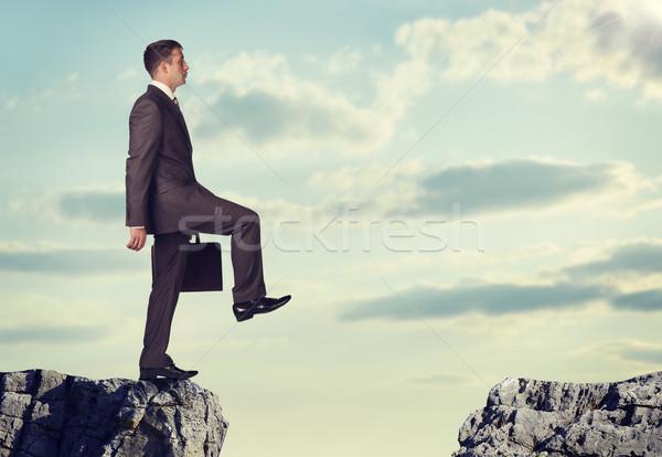 Empresário em pé borda rocha lacuna Foto stock © cherezoff