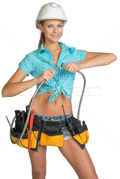 Pretty girl in helmet, shorts, shirt and tool belt with tools connects two flexible hose for plumbin Stock photo © cherezoff
