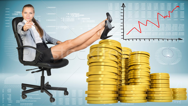 Businesswoman sitting on office chair with golden coins Stock photo © cherezoff