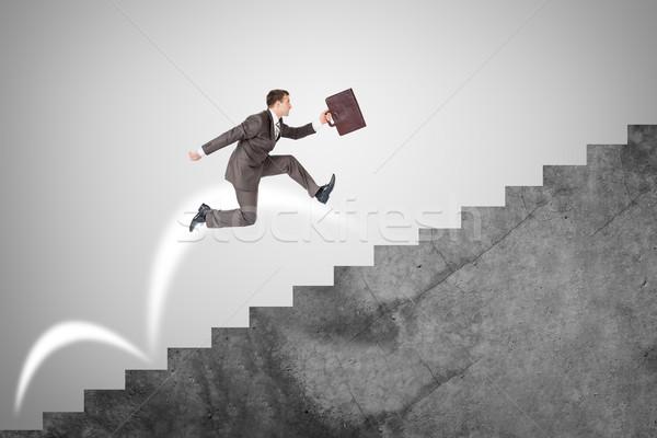 Businessman running up stairs Stock photo © cherezoff