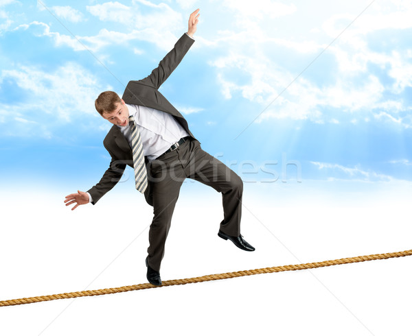 Young businessman try to walk on rope Stock photo © cherezoff